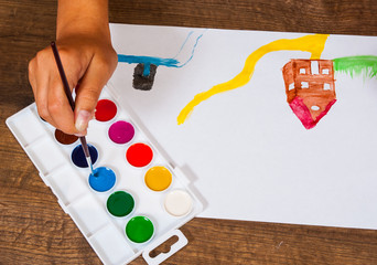 The child's hand draws a picture with watercolors. top view