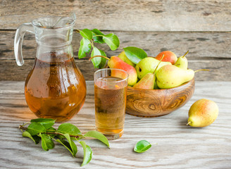 Pears in a wooden dish and a carafe of pear juice