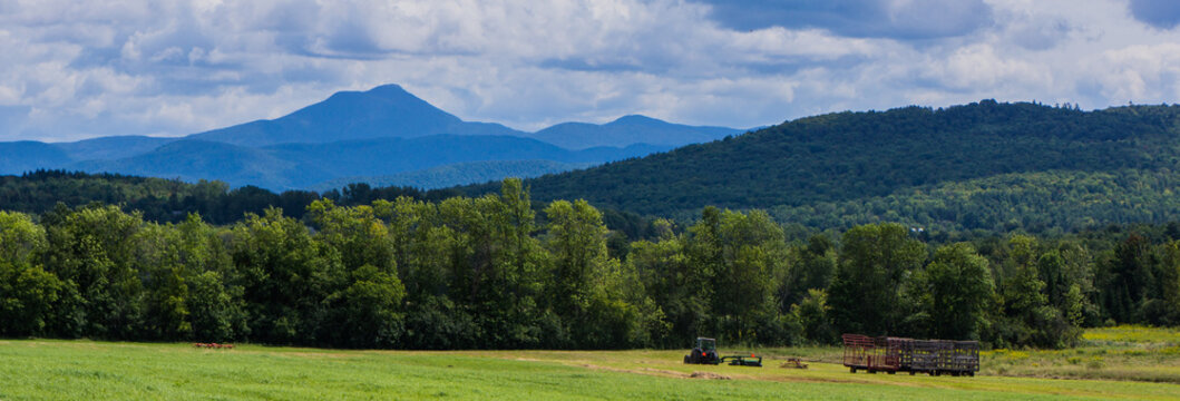 banner showing haying the fields  with view of Camels Hump Mountain , Green Mountains of Vermont