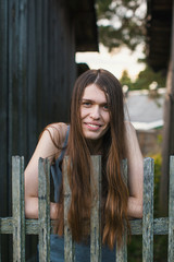 Young beautiful woman with long hair standing near the wooden fence in the village.