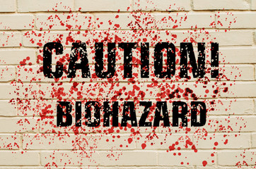 Inscription Caution Biohazard on a bloodstained brick wall