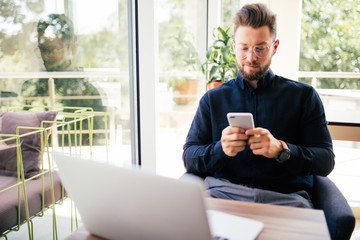 Young happy businessman smiling sitting in office with laptop while reading his smartphone. Portrait of smiling business man reading message with smartphone in office.
