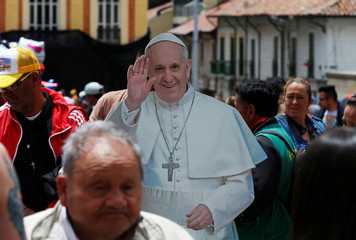 People walk past a poster with a image of Pope Francis outside the Narino Palace in Bogota