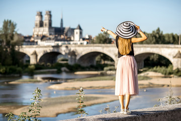 Young woman tourist standing back on the beautiful cityscape background during the sunset in Orleans city, France