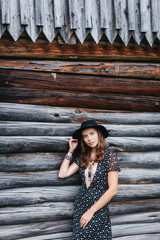 beautiful girl in black hat and black dress with stars on a wooden log wall background. Toning