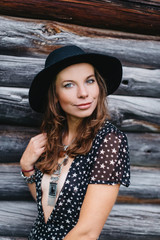 beautiful girl in black hat and black dress with stars on a wooden log wall background.