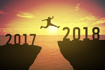 Silhouette of business man jump between 2017 and 2018 years. keep go on concept at 2018 over a beautiful sunset or sunrise at the sea. background for happy new years. success in 2018 years
