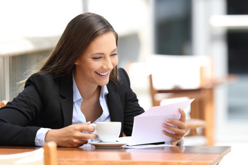 Businesswoman reading a letter in a coffee shop