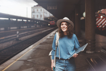 Cheerful girl waiting for train at railway station with backpack, laptop and phone