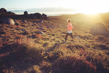 Athletic girl running around on rough terrain at sunset. Sport tight clothes. Intentional motion blur.