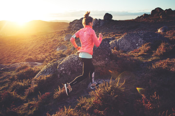 Athletic woman jogging around on rough terrain at sunset. Sport tight clothes. Intentional motion...
