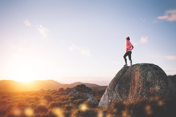 Athletic woman resting during training watching the sunset and mountain landscape. Sport tight clothes.
