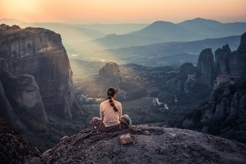 a girl watching the sunset of Meteora
