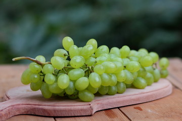 A bunch of green grapes in a wooden basket on a window