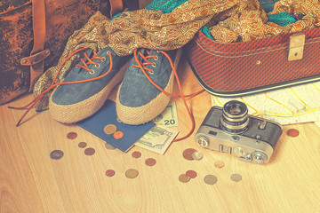Preparation for a travel. Outfit of young woman in vintage style. Different objects on wooden surface.