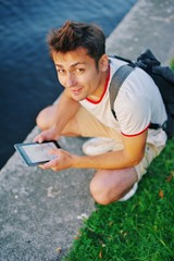 Young smiling man sitting by river and using tablet in bright Sunny day, closeup.