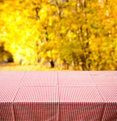 empty wooden table with autumn nature background