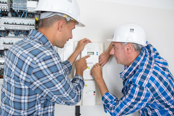 engineer adjusting temperature on thermostat