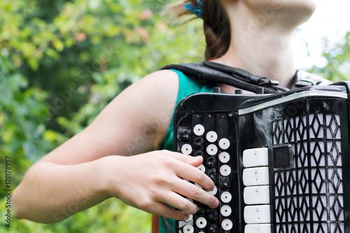 Girl musician plays the Russian bayan (button accordion)  Musician