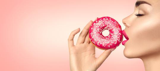 Beautiful woman eating pink donut. Beauty fashion model girl enjoying food