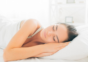 Beauty brunette girl sleeping in her comfortable bed