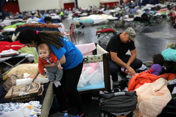 Maria Vasquez holds her son as her husband Daniel talks with their daughter while taking shelter along with thousands of others at the George R. Brown convention center after Tropical Storm Harvey flooded their home in Houston, Texas
