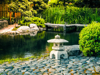 The original design of the landscape in the Japanese style. Stone lantern placed near the pond in the Japanese garden.