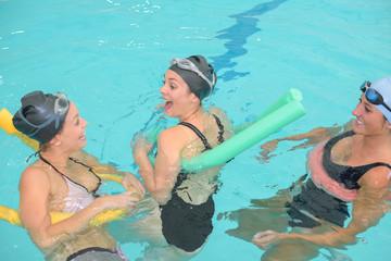 cheerful girlfriends are having fun in swimming pool