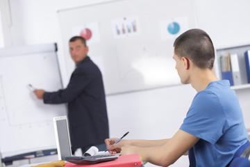 male teacher tutor near whiteboard screen giving lesson