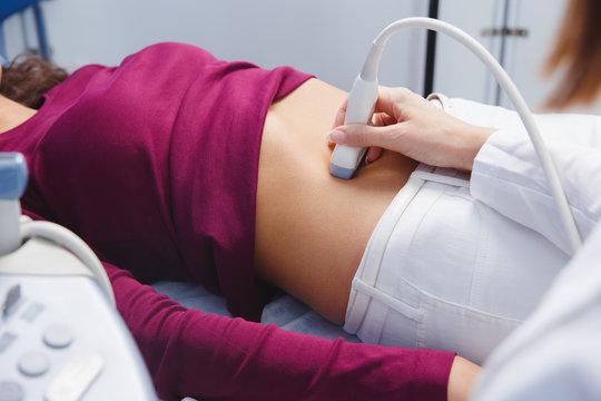 female doctor operating ultrasound scanner