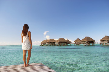 Luxury travel Tahiti vacation woman looking at overwater bungalows resort in French Polynesia. Woman on terrace deck in pristine turquoise water wearing cover-up beachwear dress relaxing.