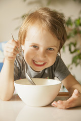 Happy cute little girl laughing and having breakfast muesli with milk at home in the kitchen (healthy food, eating, children, childhood concept )