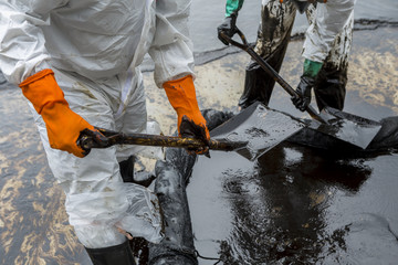 Workers remove crude oil from a beach, Crude oil on oil spill