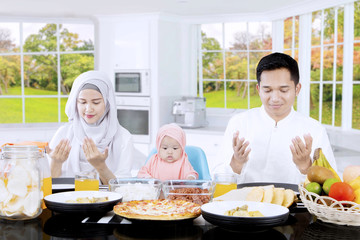 Muslim family praying together in dining table