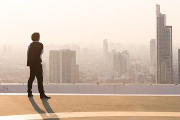 Businessman is looking at city on rooftop
