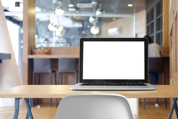 Mock up Blank screen of Laptop on marble table in Co-working or cafe.