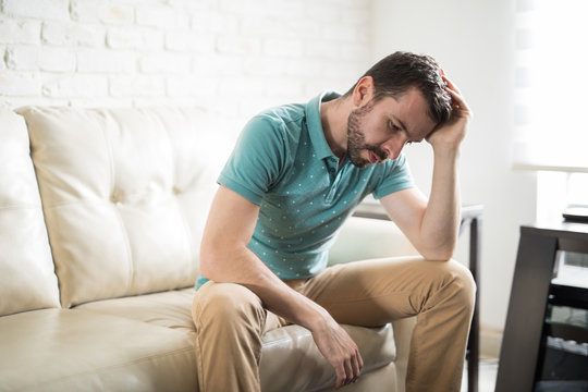Attractive man worried and alone at home