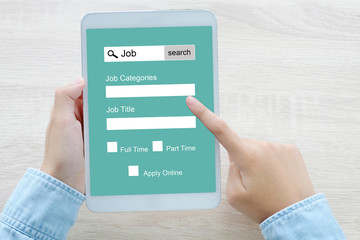 Hand using tablet searching job online on screen device, business and technology concept