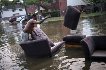 Man moves sofas onto the sidewalk from his house which was left flooded from Tropical Storm Harvey in Houston, Texas