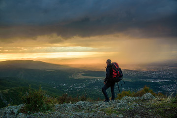 Amazing sunset on a mountain top - man with alpine equipment enjoying the breathtaking view under the stormy sky