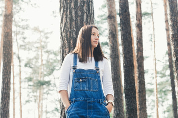 Beautiful young woman in jeans overalls standing in woodland Wall mural