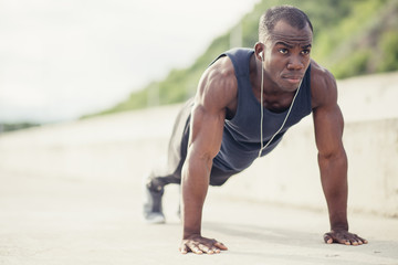 Portrait of a young black man doing push ups at the beach