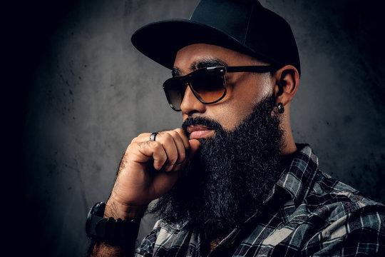 Black bearded male posing over grey background.