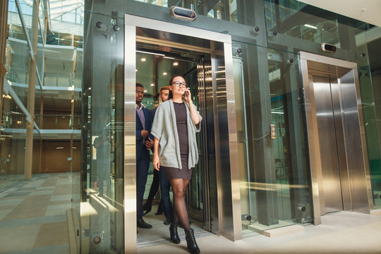 Business team group exit on elevator. Business people in a large glass elevator