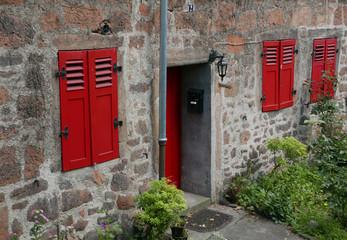 Ausschnitt einer Fassade eines alten aus Steinen gebauten Wohnhauses mit roter Tür und Fenstern mit roten Fensterläden