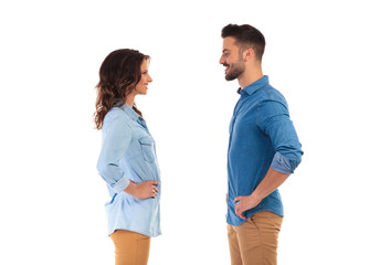casual couple standing with hands on waist facing each other