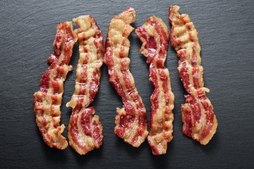 Cooked bacon rashers on the background of a slate board
