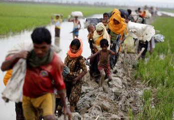 Rohingya refugees walk on the muddy path after crossing the Bangladesh-Myanmar border in Teknaf