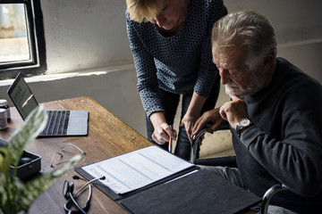 Side view of elderly man sitting on wheelchair looking at life insurance contract form