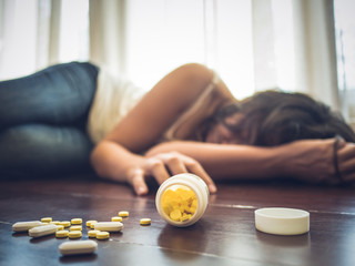 Woman taking medicine overdose and lying on the wooden floor with open pills bottle. Concept of overdose and suicide.